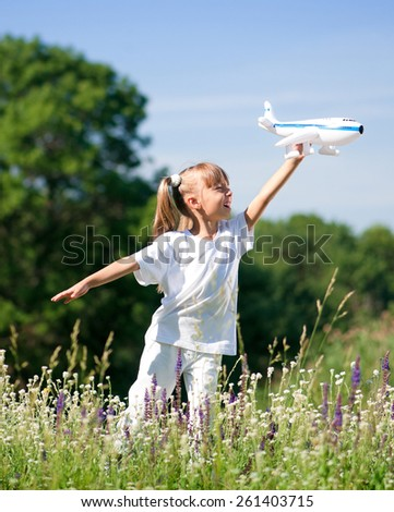 Happy little girl with plane on a meadow - stock photo