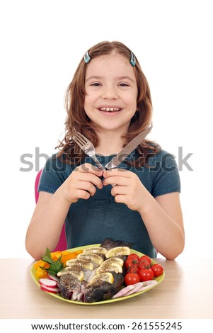 happy little girl with prepared fish on table