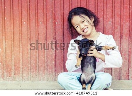 Happy little girl with puppy. - stock photo