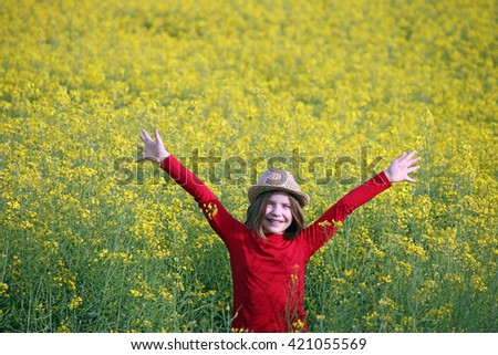 Happy little girl with straw hat and hands up on yellow field - stock photo