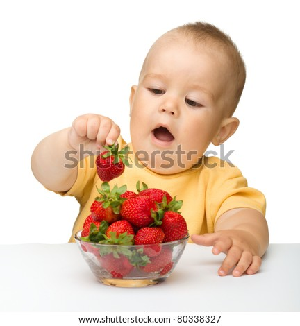 Happy little girl with strawberries, isolated over white - stock photo