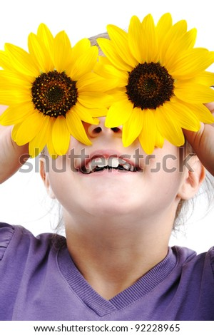 Happy little girl with sunflowers on eyes - stock photo