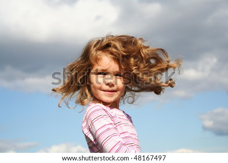 Happy little girl with the sky as background - stock photo