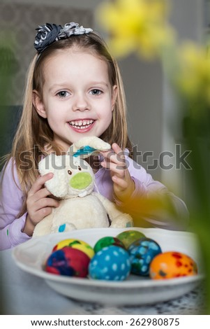 Happy little girl with toy bunny and easter eggs. Easter, holiday and child concept - stock photo