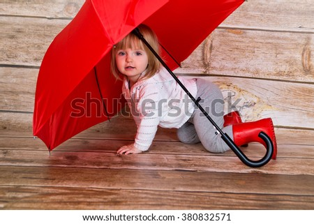 Happy Little girl with umbrella playing - stock photo