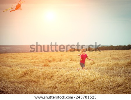 happy little girl witha kite in a field - stock photo