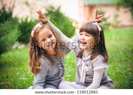 Happy little girlfriends in park - stock photo