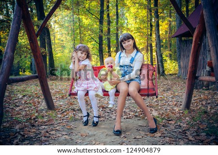 Happy little girlfriends on swing in park