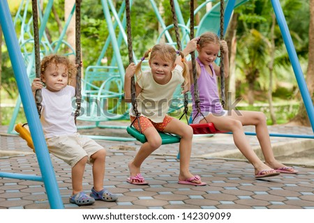 happy little girls and boy on a swing - stock photo