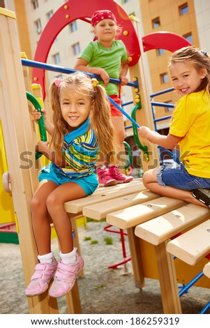 Happy little girls looking at camera while playing on playground area - stock photo