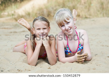 Happy little girls on sand beach at summer