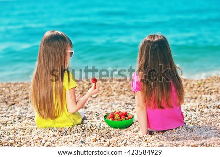Happy little girls on the sand on the beach