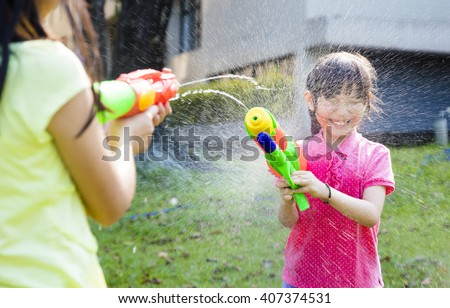 happy little girls  playing water guns in the park - stock photo