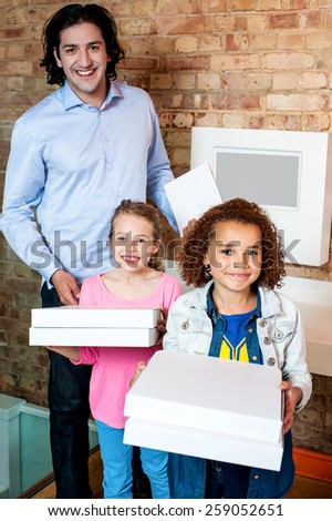 Happy little girls posing with pizza boxes - stock photo
