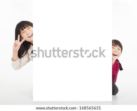 happy little girls showing blank billboard  - stock photo