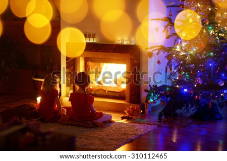Happy little girls sitting by a fireplace in a cozy dark living room on Christmas eve - stock photo