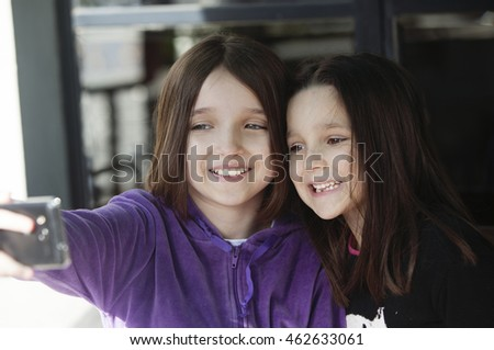 Happy little girls taking a self portrait with mobile phone
