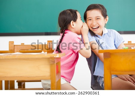 happy little girls whispering and sharing a secret  in classroom - stock photo