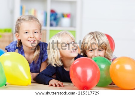 Happy little girls with colorful balloons at home