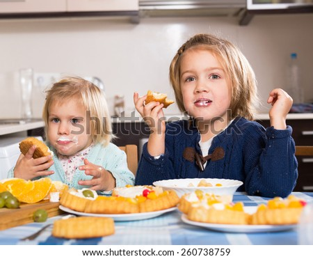 Happy little girls with stained in cream faces indoor - stock photo