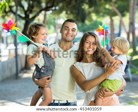 Happy little girls with windmills sitting on parent's arms outdoor. Focus on woman