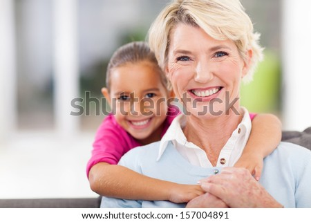 happy little granddaughter and senior grandmother at home - stock photo