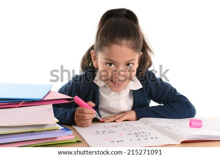 Happy little hispanic female girl writing, doing homework, studying with marker and notepad with textbooks on desk smiling in children education and back to school concept isolated on white background - stock photo