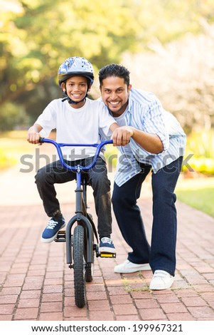 happy little indian boy learning to ride a bike with help of his father - stock photo