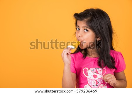 happy Little Indian girl with an ice candy or ice cream in hand, asian girl and ice cream