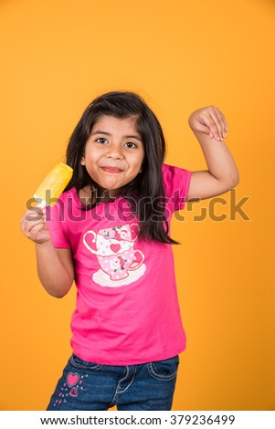 happy Little Indian girl with an ice candy or ice cream in hand, asian girl and ice cream - stock photo