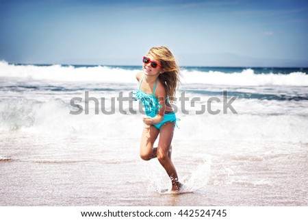 Happy little joyful girl playing on a beach, running having fun outdoors, with pleasure spending summer holidays near the sea, happy healthy childhood - stock photo