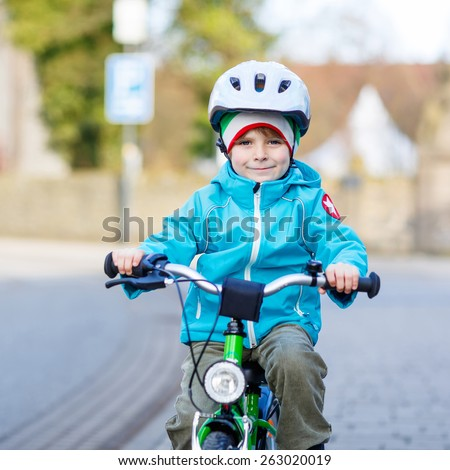 Happy little kid boy biking with his first green bike in the city. Happy child in colorful clothes. Active leisure for kids outdoors. - stock photo