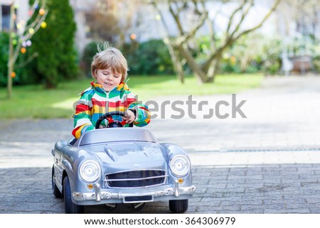 Happy little kid boy driving big toy old vintage car and having fun, outdoors. Active leisure with kids outdoors  on warm spring or autumn day. - stock photo