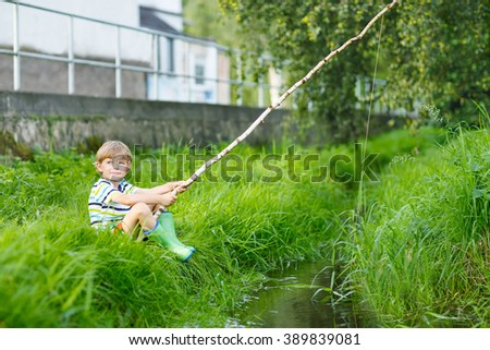 Happy little kid boy fishing on a river with selfmade fishing rod  on sunny summer day. Happy child having fun. Active leisure for children outdoors. - stock photo