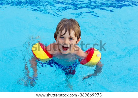 Happy little kid boy having fun in an swimming pool. Active happy child wearing safe swimmies. Family, vacations, summer concept.