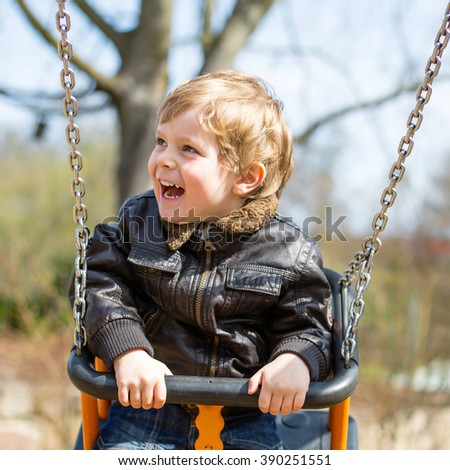 Happy little kid boy having fun on chain swing. Toddler child smiling and laughing on playground on spring day. Carefree childhood concept. - stock photo