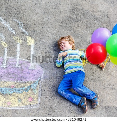 Happy little kid boy having fun with big birthday cake picture drawing with colorful chalks and balloons. Creative leisure for children outdoors in summer. - stock photo