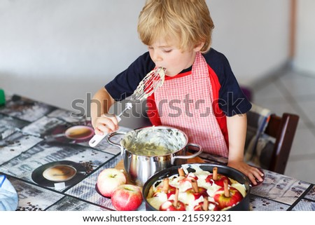 Happy little kid boy helping and baking apple pie in home''s kitchen, indoor. Tasting vanilla dough. - stock photo