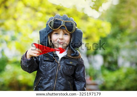 Happy little kid boy in pilot helmet  and uniform playing with red toy airplane against green tree summer background. Child having fun and dreaming of future profession. - stock photo