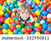 Happy little kid boy playing at colorful plastic balls playground high view. Adorable child having fun indoors. - stock photo