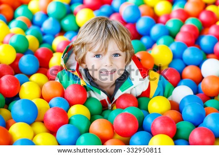 Happy little kid boy playing at colorful plastic balls playground high view. Adorable child having fun indoors.