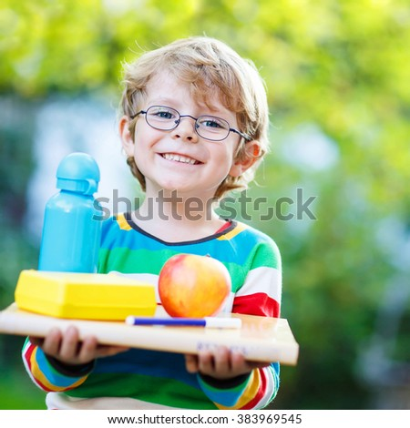 Happy little kid boy with books, apple and drink bottle on his first day to elementary school or nursery. Outdoors.  Back to school, kids, lifestyle concept - stock photo