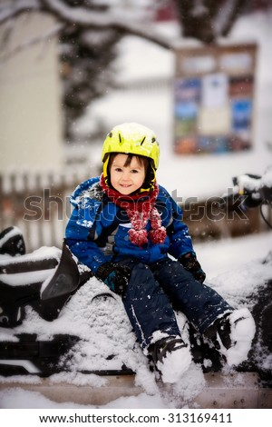Happy little kid is playing in snow, good winter weather, ski gear, sitting on a snow motor sledge