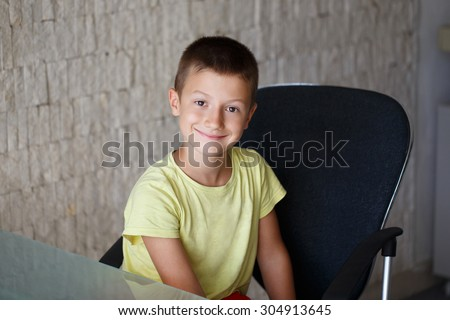 Happy little kid sit at glass desk in office