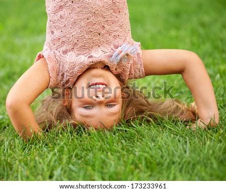 Happy little kid standing on his head in the Spring Park. Recreation and fun concept. - stock photo