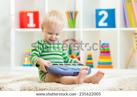 Happy little kid toddler boy having fun playing piano toy sitting on floor in nursery - stock photo