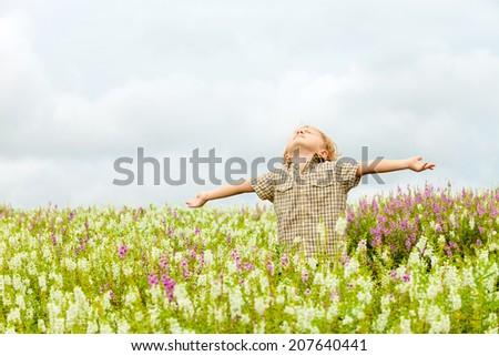 Happy little kid with raised up arms in green  field of flowers. Concept of freedom and happiness. - stock photo