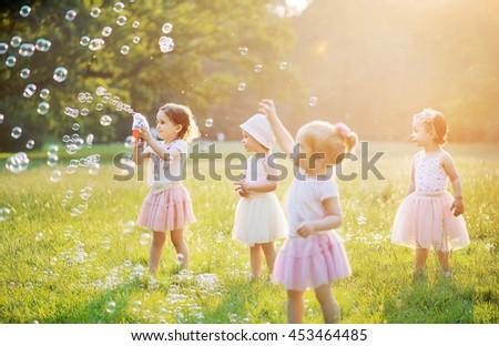 Happy little kids blowing soap bubbles in summer park - stock photo