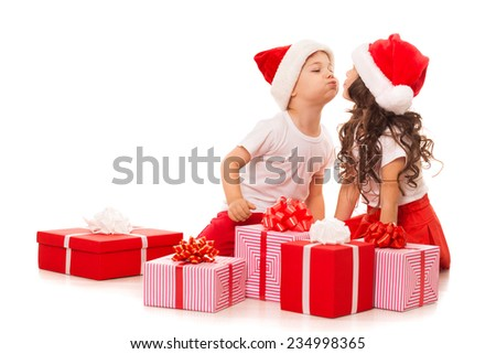 Happy little kids in Santa hat with Christmas gift boxes. Isolated on white background. Space for Your Text. Sale, holidays, christmas, new year, x-mas concept.