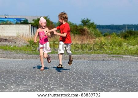 happy little kids running in street - stock photo